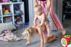 Frère et soeur avec la mère riant et ayant l'amusement d'intérieur Le garçon infantile jouant, soeur plus âgée de monte de retour photos stock