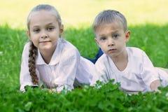 Frère et soeur détendant en parc Photo stock