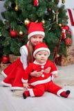 Frère et soeur dans des vêtements de Noël Regard de famille Photos stock
