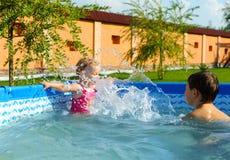 Frère et soeur dans la piscine Image libre de droits