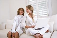 Frère et soeur dans le blanc sur le sofa utilisant l'ordinateur portatif photographie stock libre de droits