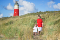Frère et soeur gais sur la plage à côté du phare Images stock
