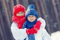 Frère et soeur heureux en bonhomme de neige de costumes marchant dans la forêt d'hiver, Photos stock