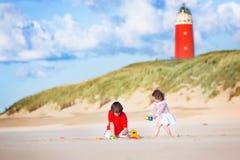 Frère et soeur heureux sur la plage à côté du phare Images libres de droits