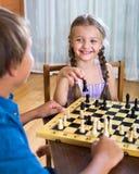 Frère et soeur jouant aux échecs Image stock