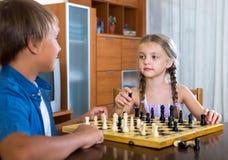 Frère et soeur jouant aux échecs Photos libres de droits
