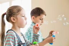 Frère et soeur jouant avec des baguettes magiques de bulle à la maison Image libre de droits