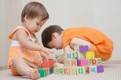 Frère et soeur jouant avec des cubes en jouet photographie stock