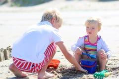 Frère et soeur jouant avec le sable sur la plage Images stock
