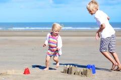Frère et soeur jouant avec le sable sur la plage Photo stock