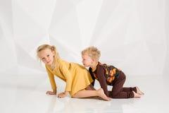 Frère et soeur jouant et souriant dans un studio blanc Photographie stock libre de droits