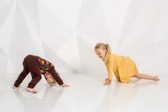 Frère et soeur jouant et souriant dans un studio blanc Photo stock