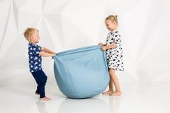 Frère et soeur jouant et souriant dans un studio blanc Image stock