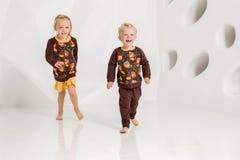 Frère et soeur jouant et souriant dans un studio blanc Photos libres de droits