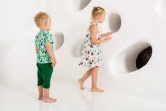 Frère et soeur jouant et souriant dans un studio blanc Photographie stock