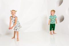 Frère et soeur jouant et souriant dans un studio blanc Image libre de droits