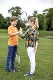 Frère et soeur jouant le badminton sur le champ vert Photos stock