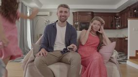 Frère et soeur jouant le fonctionnement autour des parents, la fille jouant l'ukulélé, garçon jouant avec la boule Mère confuse e banque de vidéos