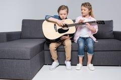 Frère et soeur jouant sur la guitare ensemble tout en se reposant sur le sofa Photos stock