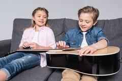 Frère et soeur jouant sur la guitare ensemble tout en se reposant sur le sofa Images libres de droits