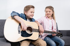 Frère et soeur jouant sur la guitare ensemble tout en se reposant sur le sofa Images stock