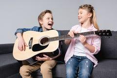 Frère et soeur jouant sur la guitare et chantant ensemble tout en se reposant sur le sofa Images libres de droits