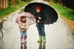 Frère et soeur marchant sous la pluie tenant des parapluies Image stock