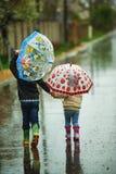 Frère et soeur marchant sous la pluie tenant des parapluies Photo libre de droits