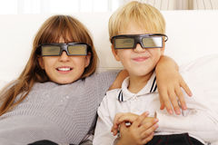 Frère et soeur observant le film 3D Photos libres de droits