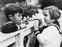 Frère et soeur parlant les uns avec les autres (toutes les personnes représentées ne sont pas plus long vivantes et aucun domaine Photographie stock