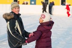 Frère et soeur patinant sur la piste main dans la main Image stock