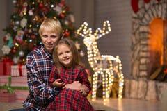 Frère et soeur près de l'arbre de Noël photos stock