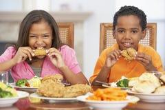 Frère et soeur prenant le déjeuner à la maison photographie stock libre de droits