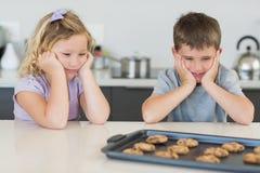 Frère et soeur regardant des biscuits de tentation Photo libre de droits