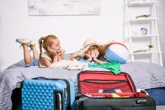 frère et soeur s'étendant sur le lit avec des valises Photos stock