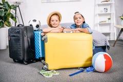 frère et soeur s'étendant sur le lit avec des valises Photos libres de droits