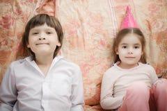 Frère et soeur s'asseyant à la maison photos stock