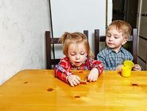 Frère et soeur s'asseyant à la table de cuisine Photos libres de droits