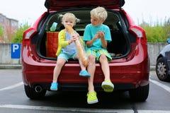 Frère et soeur s'asseyant dans la voiture familiale Photographie stock libre de droits