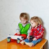 Frère et soeur s'asseyant sur la table de cuisine avec la tablette et le p Photographie stock