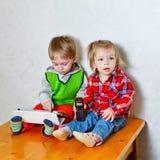 Frère et soeur s'asseyant sur la table de cuisine avec la tablette et le p Photo stock