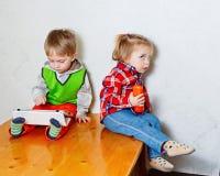 Frère et soeur s'asseyant sur la table de cuisine avec la tablette et le p Images libres de droits