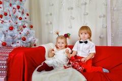 Frère et soeur s'asseyant sur le divan près de l'arbre de Noël Image libre de droits