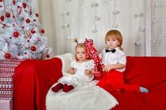 Frère et soeur s'asseyant sur le divan près de l'arbre de Noël images stock