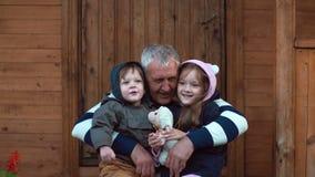 Frère et soeur s'asseyant sur les genoux du grand-père s Le vieil homme étreint son petit-fils et petite-fille 4K Photos libres de droits