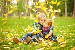 Frère et soeur s'asseyant sur une herbe Images stock
