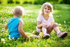 Frère et soeur s'asseyant sur une herbe Photographie stock