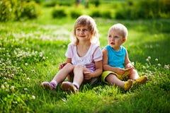 Frère et soeur s'asseyant sur une herbe Photos stock