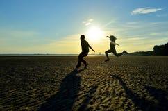 Frère et soeur sautant sur la plage Photographie stock libre de droits