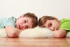 Frère et soeur se trouvant sur l'étage sur la peau Image stock